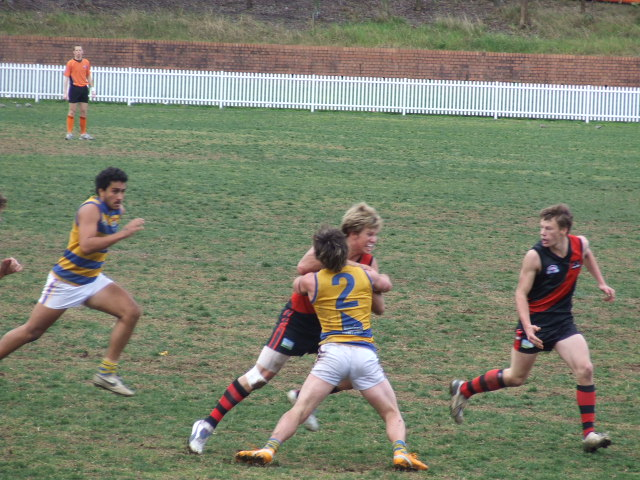 Sydney Uni's Brydon Coles tackles North Shore's Lachlan Pryor